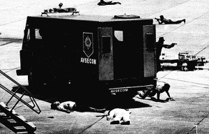 Aquino's body in the foreground. His assassin's body next to the police van